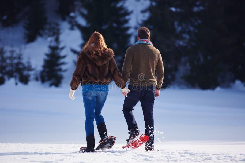 Paar die pret hebben en in sneeuwschoenen lopen stock foto's