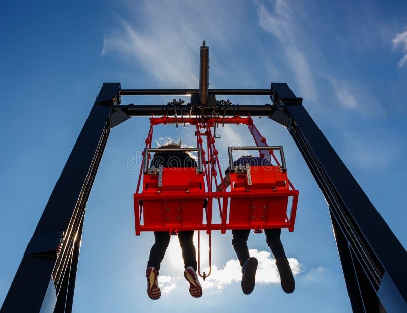 Paar die pret in schommeling op een hoog gebouw hebben tegen blauwe hemel stock fotografie