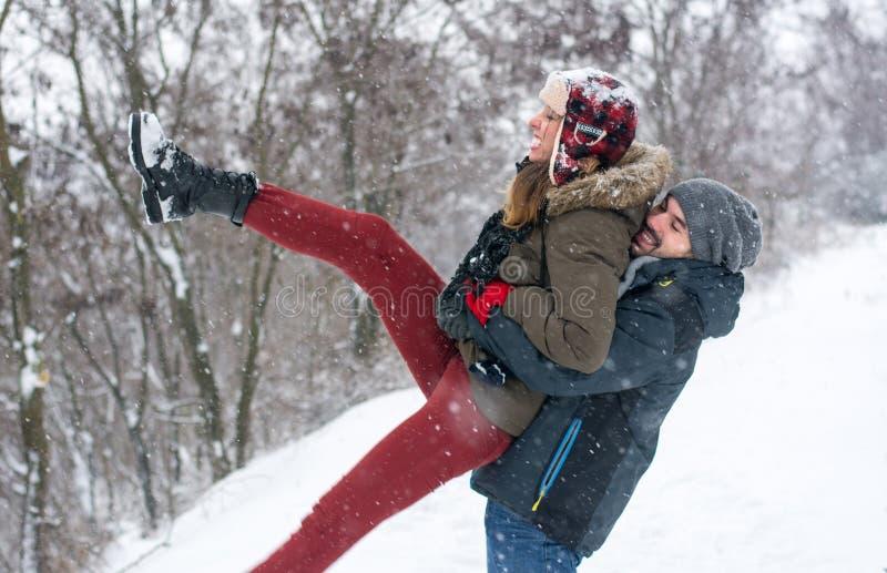 Paar die pret in sneeuw behandeld park hebben stock foto