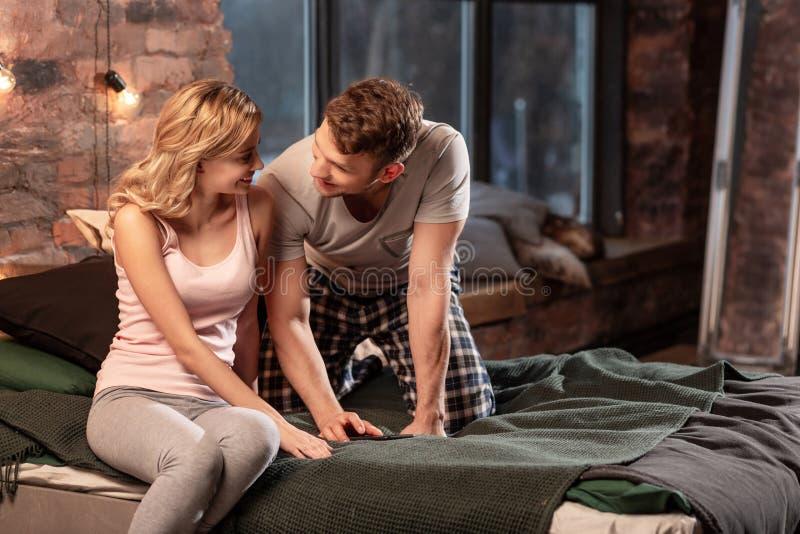 Paar die pyjama's dragen die smartphone gebruiken terwijl het liggen in bed royalty-vrije stock foto
