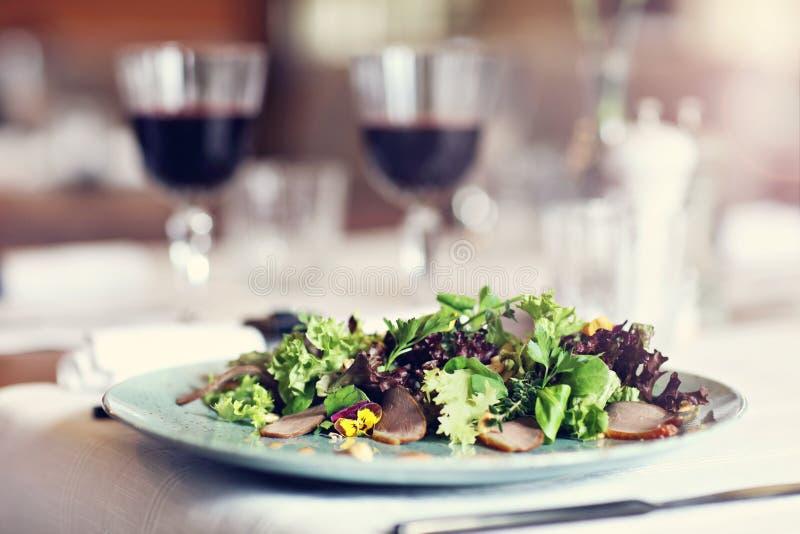 Paar die romantisch Diner in een gastronomische restaurant het drinken wijn eten en het eten stock afbeelding