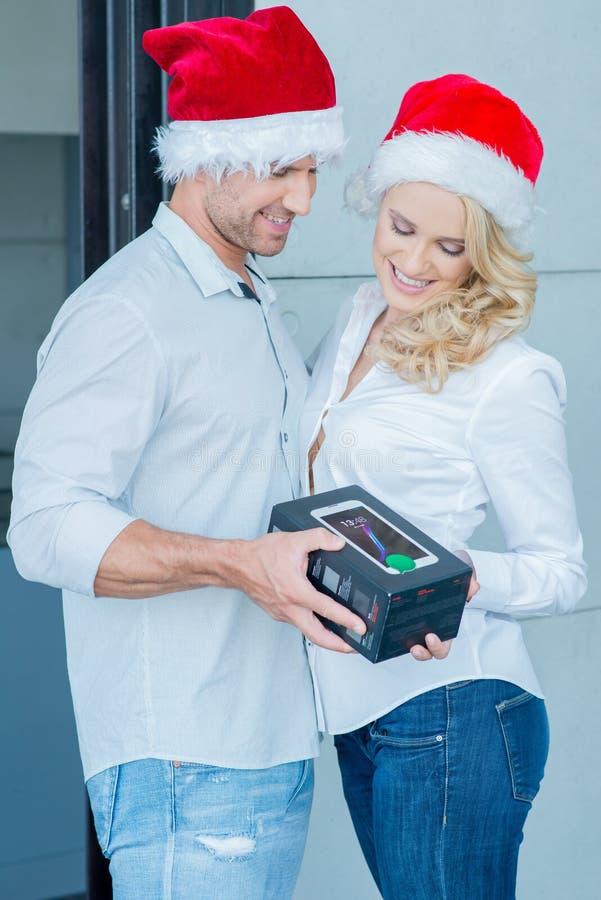 Paar die Santa Hats Exchanging Gift dragen royalty-vrije stock fotografie