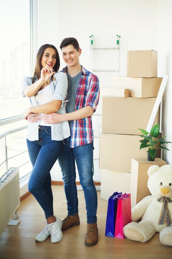 Paar die sleutels tonen aan nieuw huis die, samen uitpakkende kaart koesteren royalty-vrije stock fotografie
