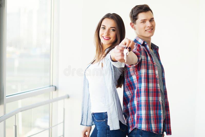 Paar die sleutels tonen aan nieuw huis die, samen uitpakkende kaart koesteren royalty-vrije stock afbeeldingen