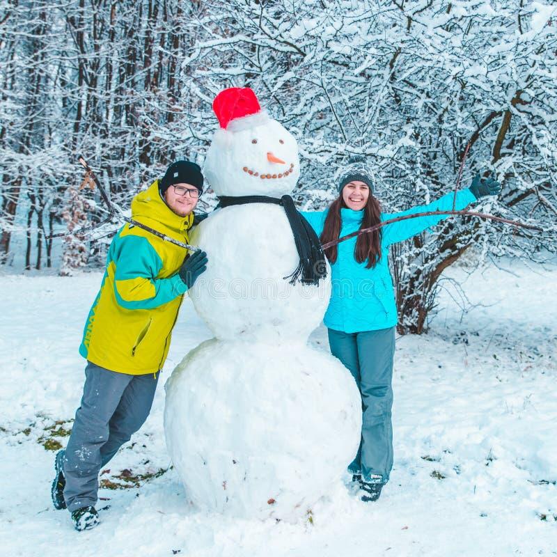 Paar die sneeuwman in bevroren de winterdag maken royalty-vrije stock foto's