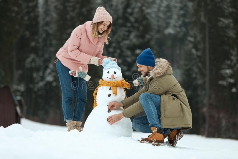 Paar die sneeuwman in openlucht maken De winter stock afbeelding