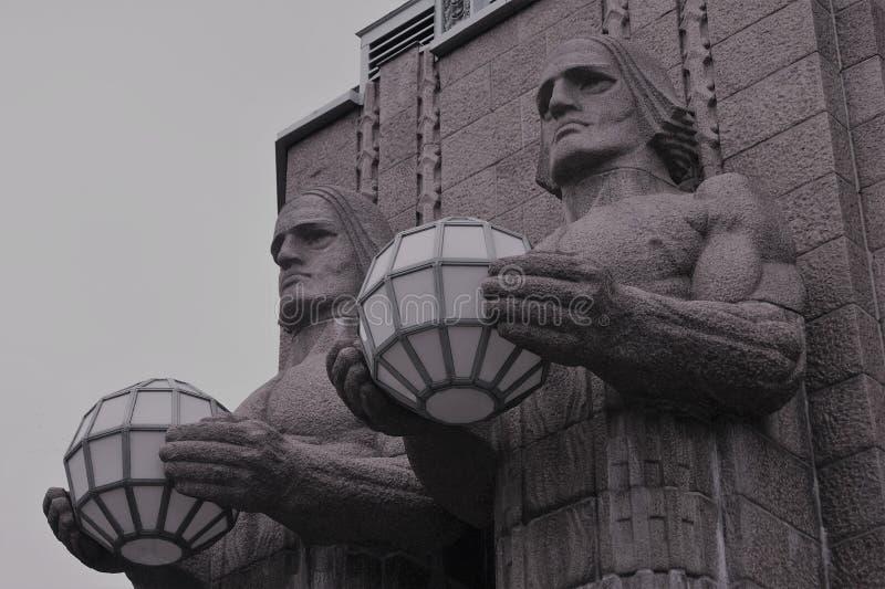 Paar die standbeelden straatlantaarns op de muur van het Centrale Station van Helsinki houden stock foto