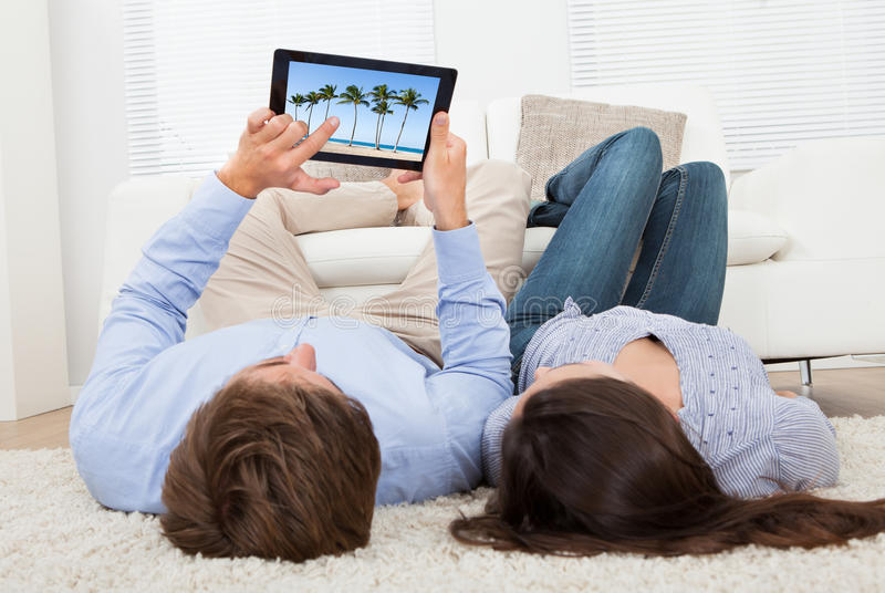 Paar die strandfoto bekijken op digitale tablet stock fotografie