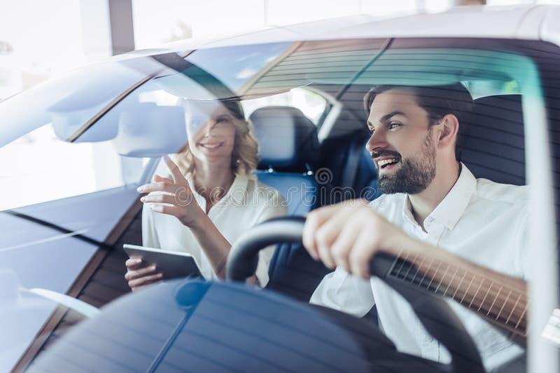 Paar die terwijl het drijven van een auto spreken stock afbeeldingen