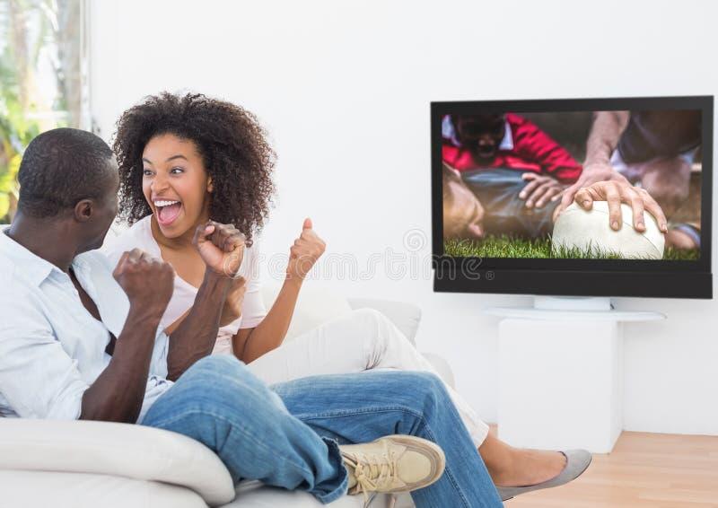 Paar die terwijl het letten van rugby op gelijke op televisie toejuichen stock foto's
