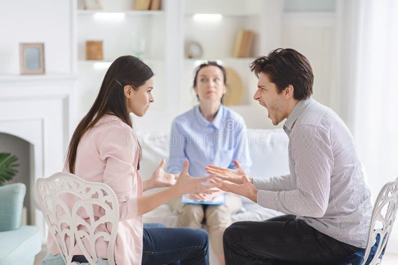 Paar die tijdens therapiezitting debatteren met psycholoog royalty-vrije stock foto