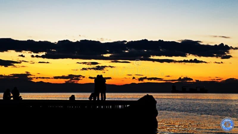 Paar die tijdens zonsondergang koesteren royalty-vrije stock fotografie