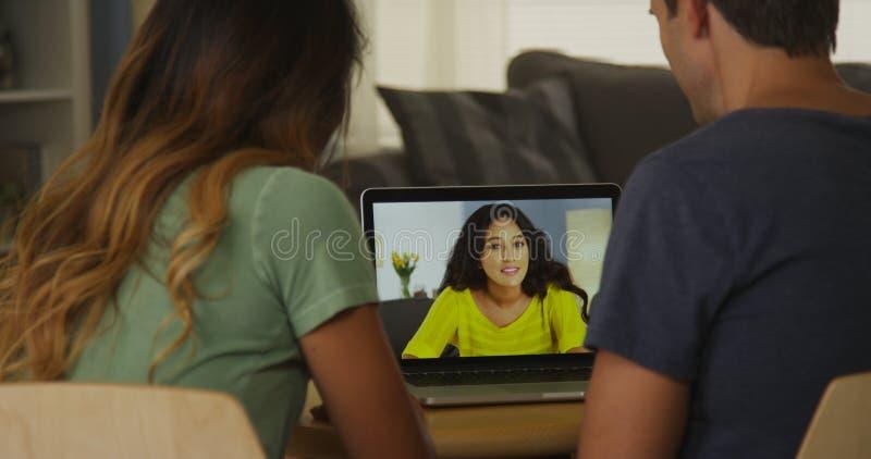 Paar die tussen verschillende rassen met een online vriend spreken stock afbeeldingen