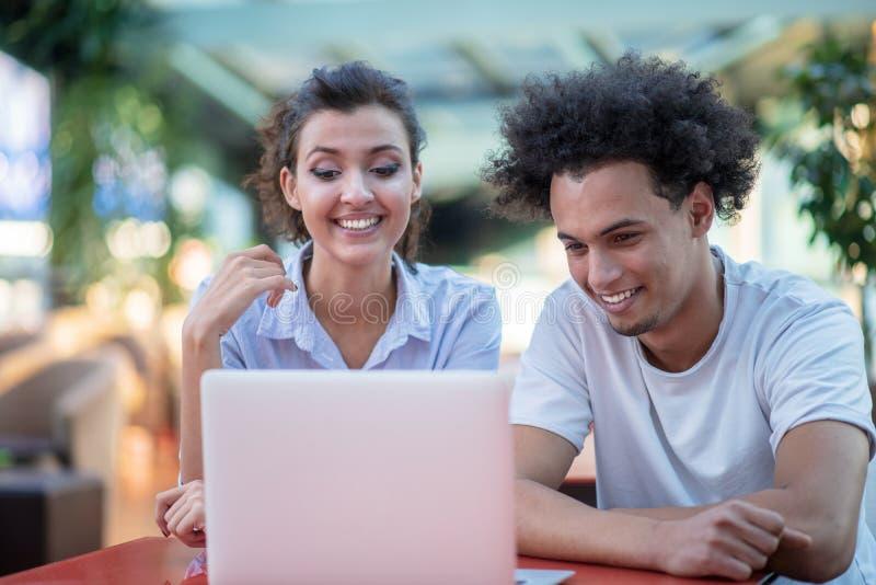Paar die tussen verschillende rassen tabletcomputer in koffiewinkel met behulp van stock fotografie