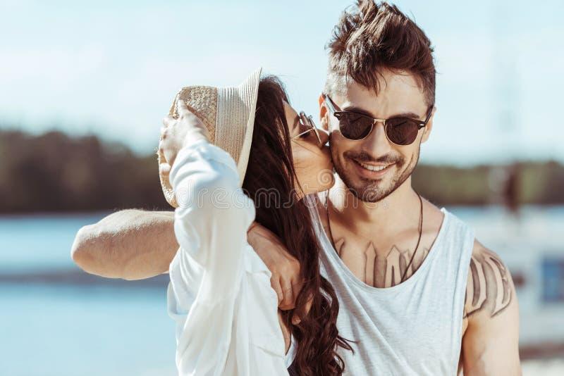 Paar die tussen verschillende rassen in zonnebril terwijl meisje die haar vriend kussen koesteren stock foto