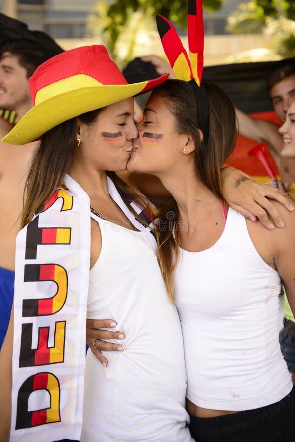 Paar die van Duitse het voetbalventilators van de vrouwensport elkaar kussen. royalty-vrije stock fotografie