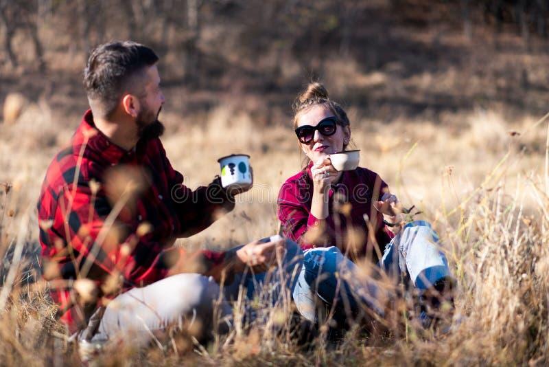 Paar die van een kop van koffie op een picknick genieten royalty-vrije stock foto