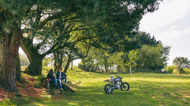 Paar die van een motorfietsreis rusten stock afbeeldingen