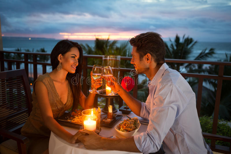 Paar die van een romantisch diner genieten door kaarslicht stock afbeeldingen