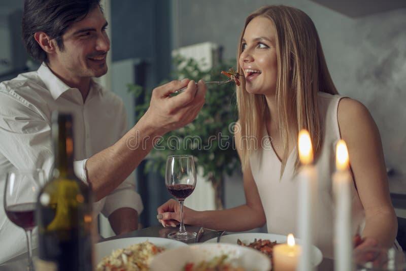 Paar die van een romantisch diner genieten door kaarslicht stock afbeelding