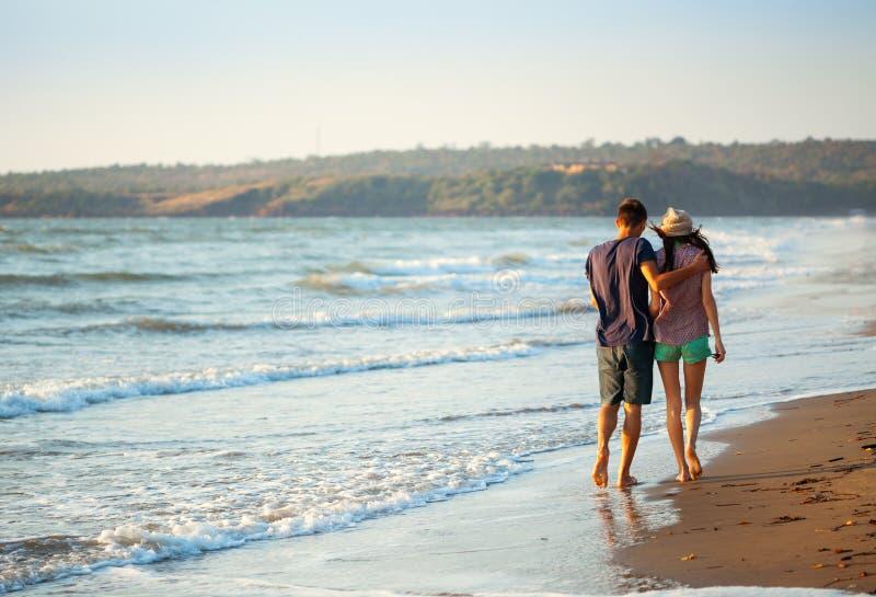 Paar die van een romantische avond op het strand genieten bij zonsondergang stock afbeelding