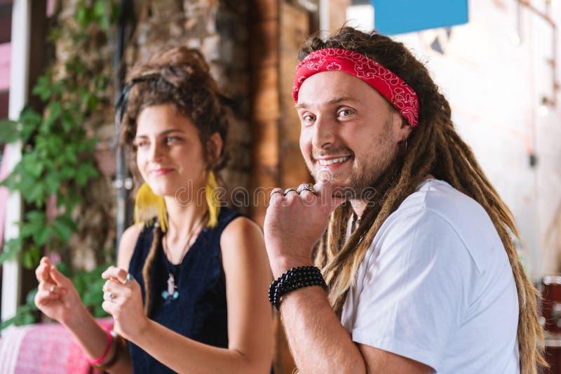Paar die van gelukkige modieuze hippies in koffie zitten royalty-vrije stock afbeeldingen