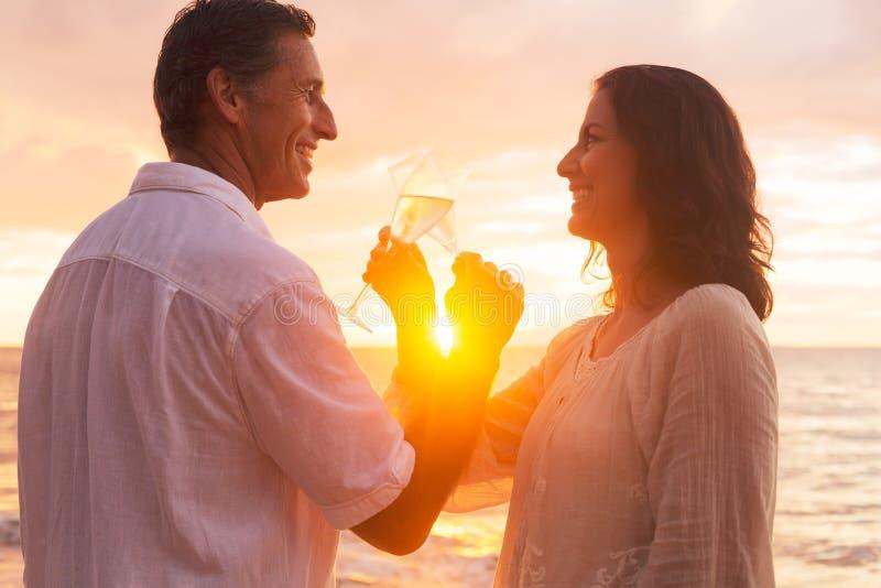 Paar die van Glas van Champene op het Strand genieten bij Zonsondergang stock foto