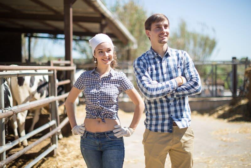 Paar die van landbouwbedrijfwarkers bij koeiestal stellen royalty-vrije stock foto's