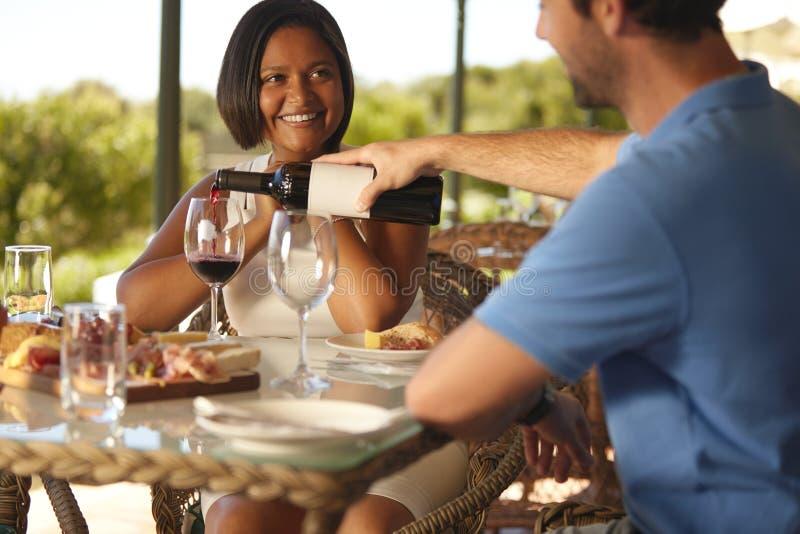 Paar die van rode wijn genieten bij wijnmakerijrestaurant royalty-vrije stock foto