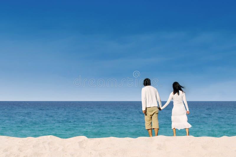Paar die van wittebroodsweken genieten bij het strand stock foto