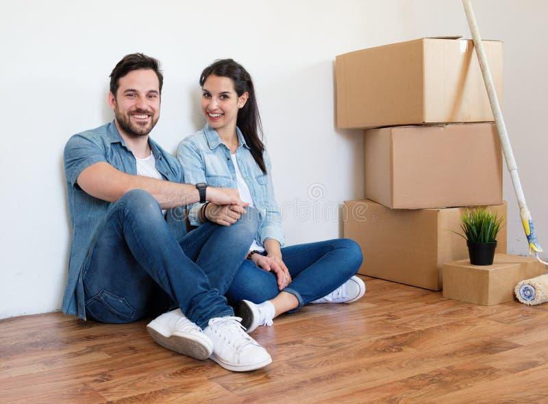 Paar die of verpakkingsdozen en het bewegen zich in een nieuw huis uitpakken stock afbeeldingen