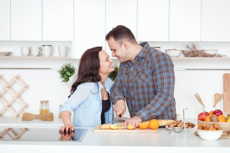 Paar die vers organisch sap in keuken samen maken Een jonge mens snijdt een baguette Een vrouw die zich dichtbij haar bevinden royalty-vrije stock foto