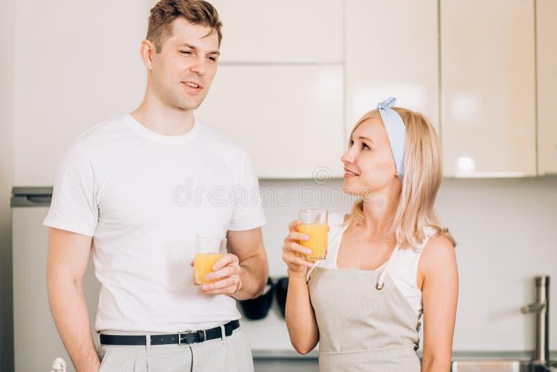 Paar die vers organisch sap in keuken samen maken royalty-vrije stock afbeelding