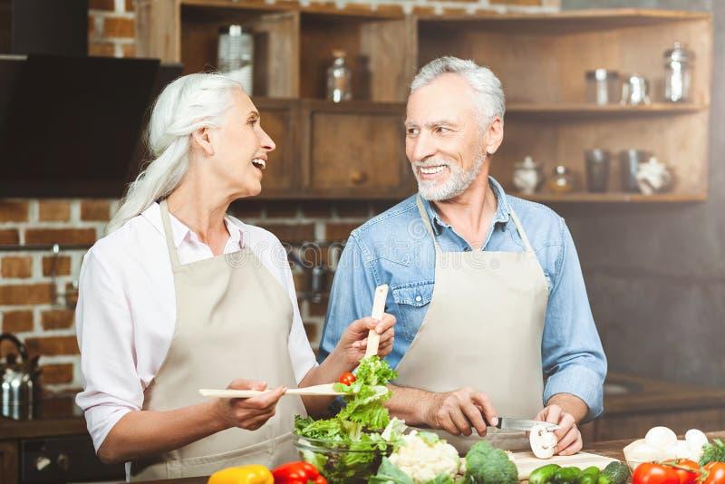 Paar die voedsel voorbereiden bij de keuken stock foto's