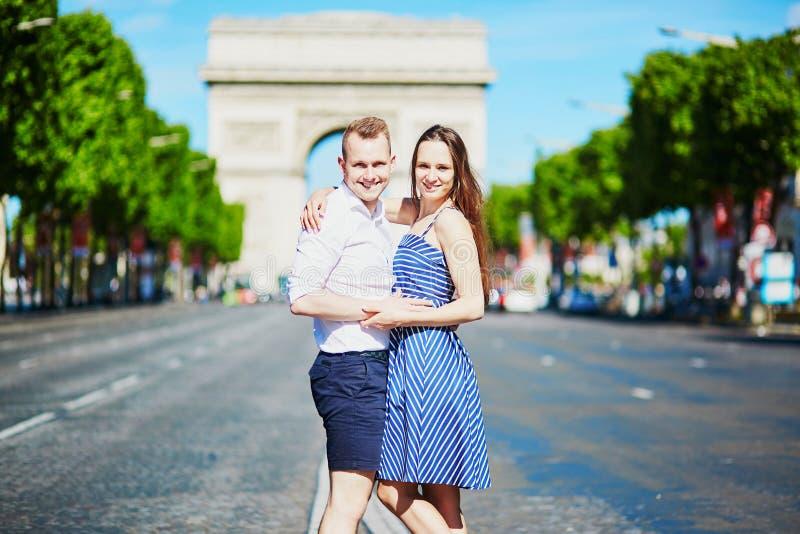 Paar die voor Triomfantelijke boog in Parijs lopen stock afbeeldingen