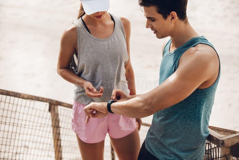 Paar die wearable technologie gebruiken tijdens training royalty-vrije stock foto