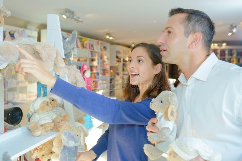 Paar die in winkel zacht speelgoed bekijken stock afbeelding