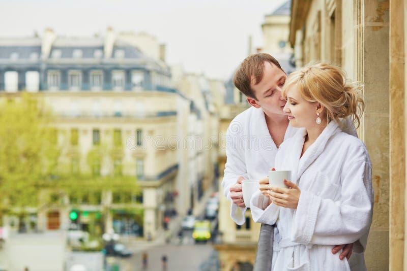 Paar die in witte badjassen koffie samen op balkon drinken stock fotografie