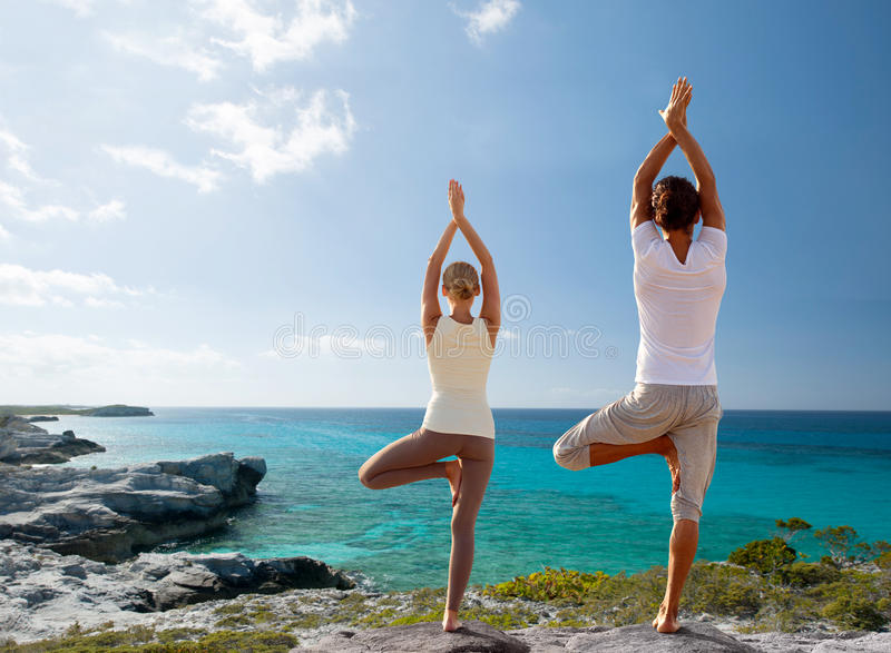 Paar die yogaoefeningen op strand van rug maken stock afbeeldingen