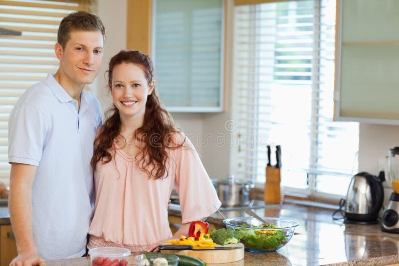 Paar die zich achter keukenteller bevinden stock afbeelding