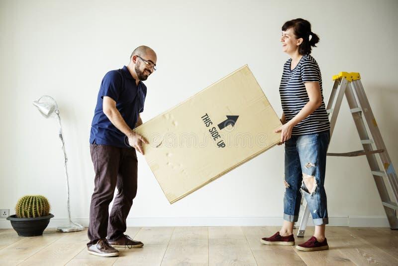 Paar die zich binnen in nieuw huis bewegen royalty-vrije stock foto