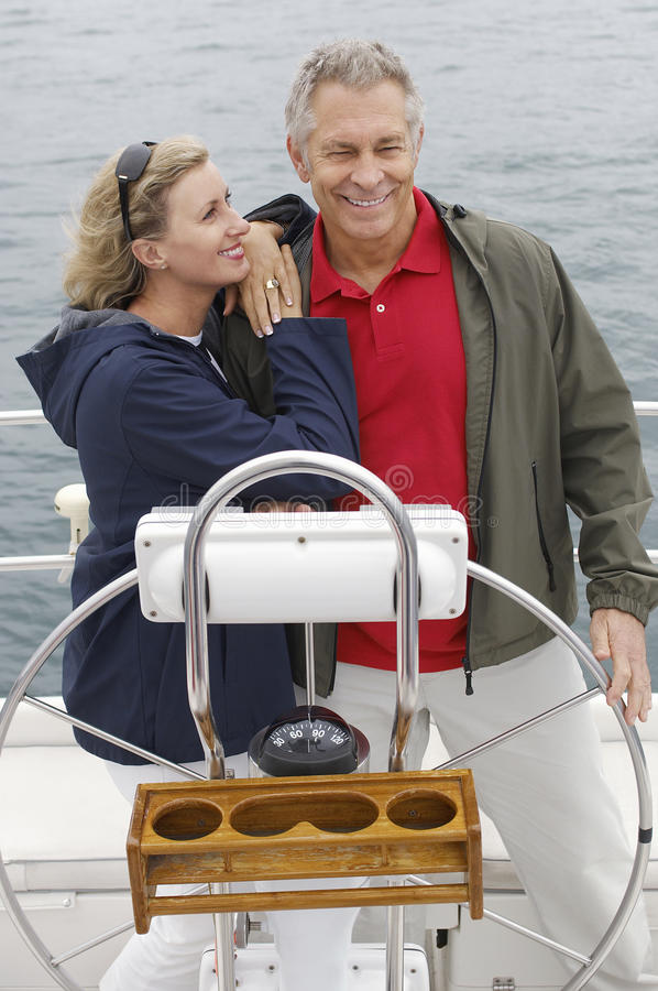 Paar die zich door Roer op Zeilboot bevinden stock fotografie