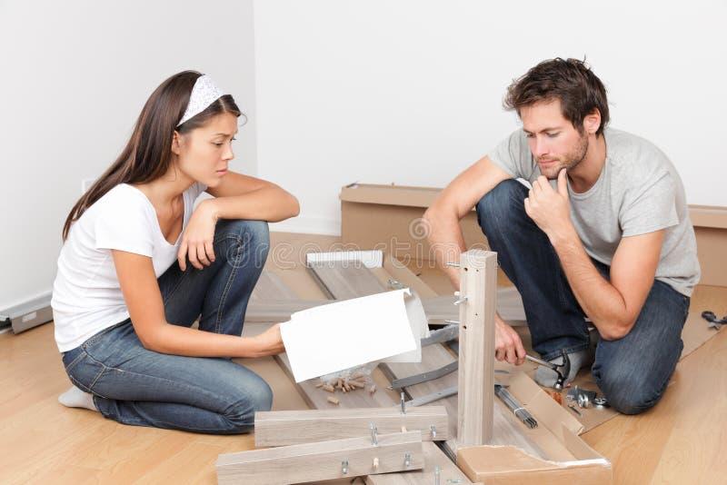 Paar die zich in het assembleren van bedmeubilair bewegen stock afbeelding
