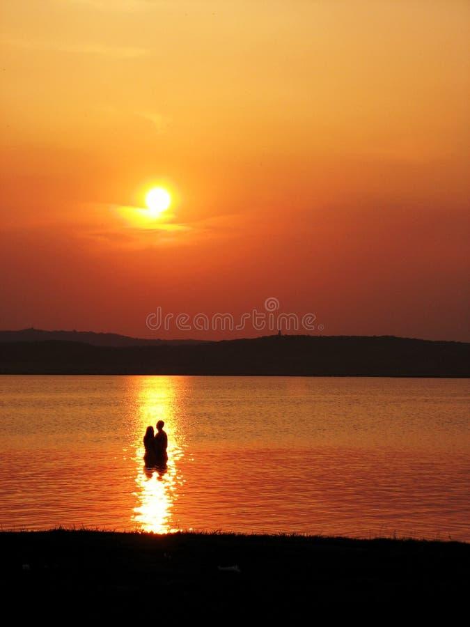 Paar die zich in het water bij zonsondergang bevinden