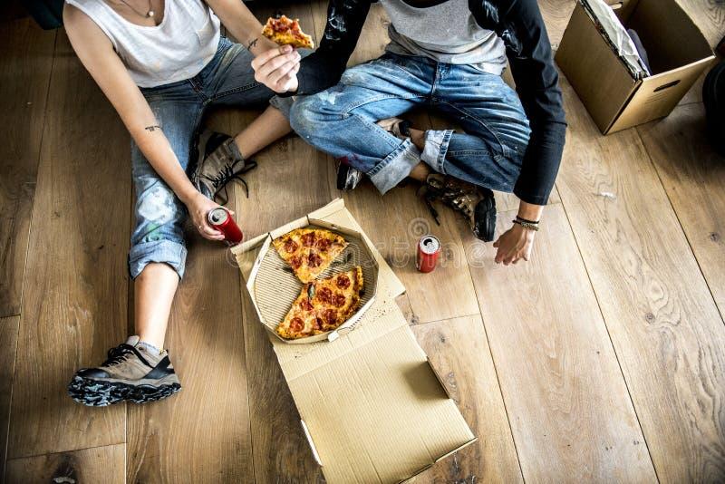 Paar die zich in nieuw huis bewegen die pizza eten royalty-vrije stock fotografie
