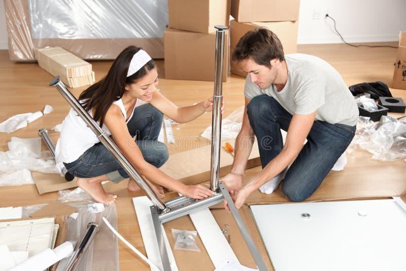 Paar die zich in samen het assembleren van meubilairlijst bewegen royalty-vrije stock foto