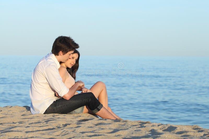 Paar die zitting op het zand van het strand koesteren stock foto's