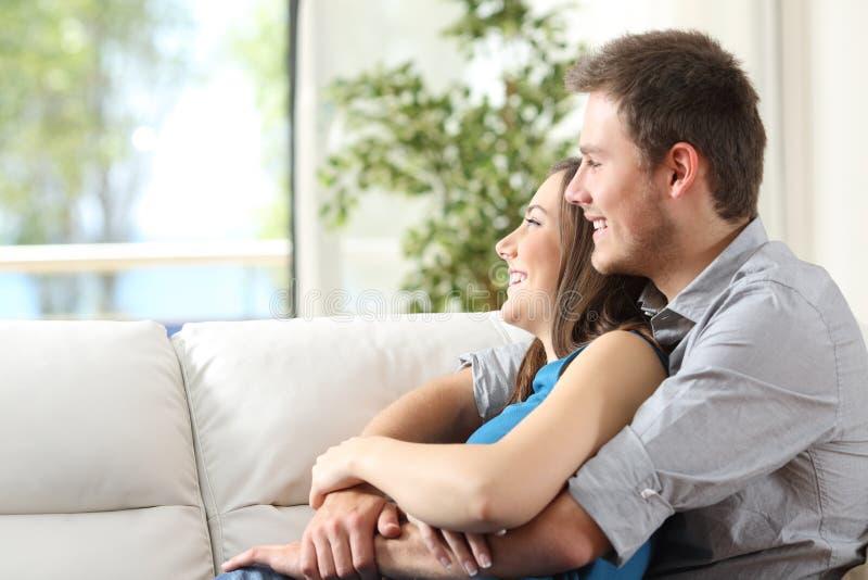 Paar die zitting op laag thuis koesteren stock afbeelding