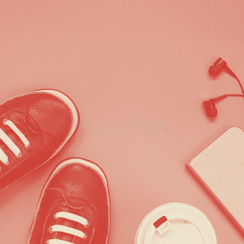 Paar donkere sportschoenen met wit schoenkant, kop van koffie, mobiele dekking en zwarte oortelefoons in lager deel van stock afbeeldingen