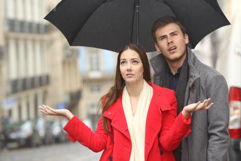 Paar in een regenachtige dag wordt geërgerd die royalty-vrije stock afbeelding